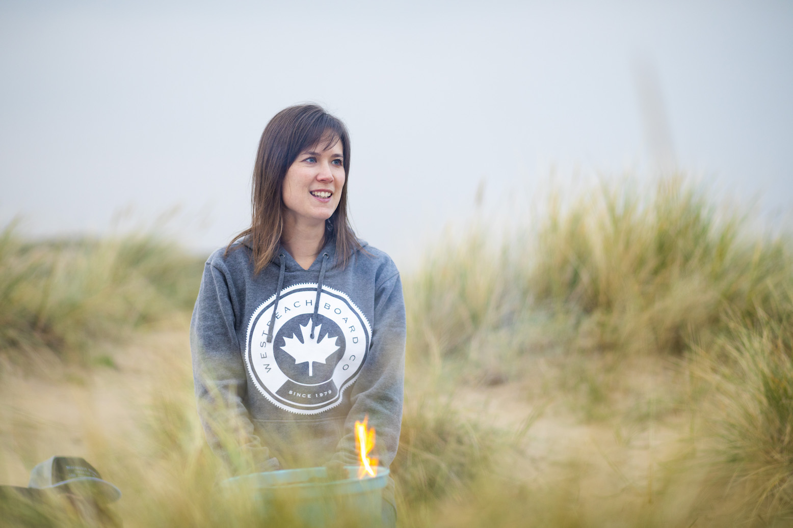 An image of myself sat in the sand dunes at Camber Sands wearing a grey hoodie from West Beach